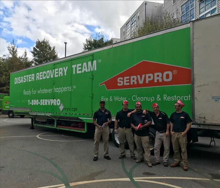 SERVPRO techs standing in front of our trailer parked in the parking lot