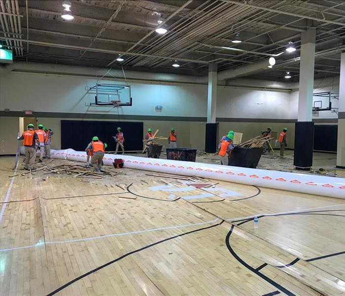 SERVPRO technicians removing the floor of a basketball court in Nashville after water damage