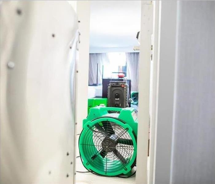 Close up of an air mover way behind a dehumidifier in a home